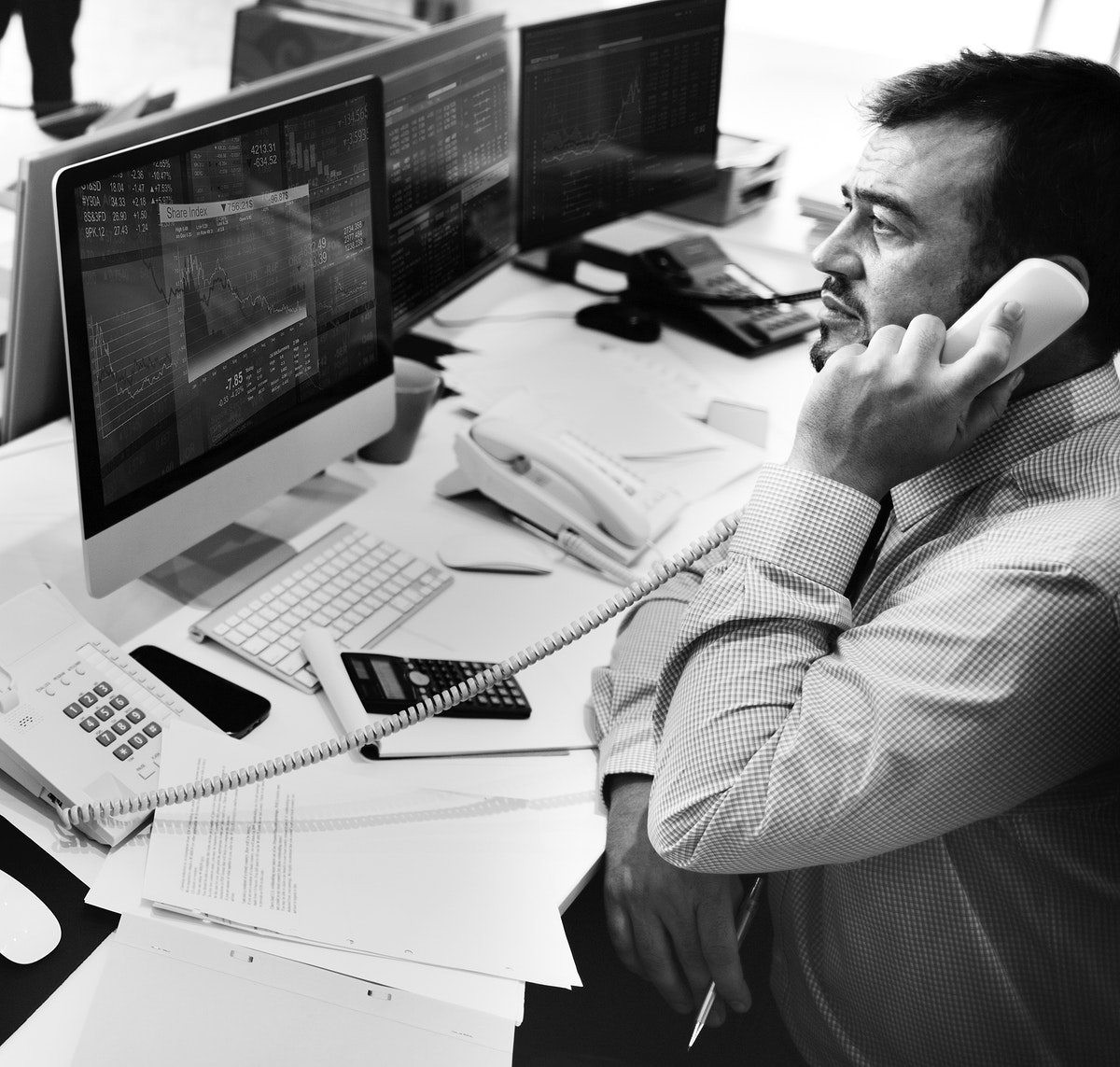 Man talking on the phone looking at stock market analysis on computer screen