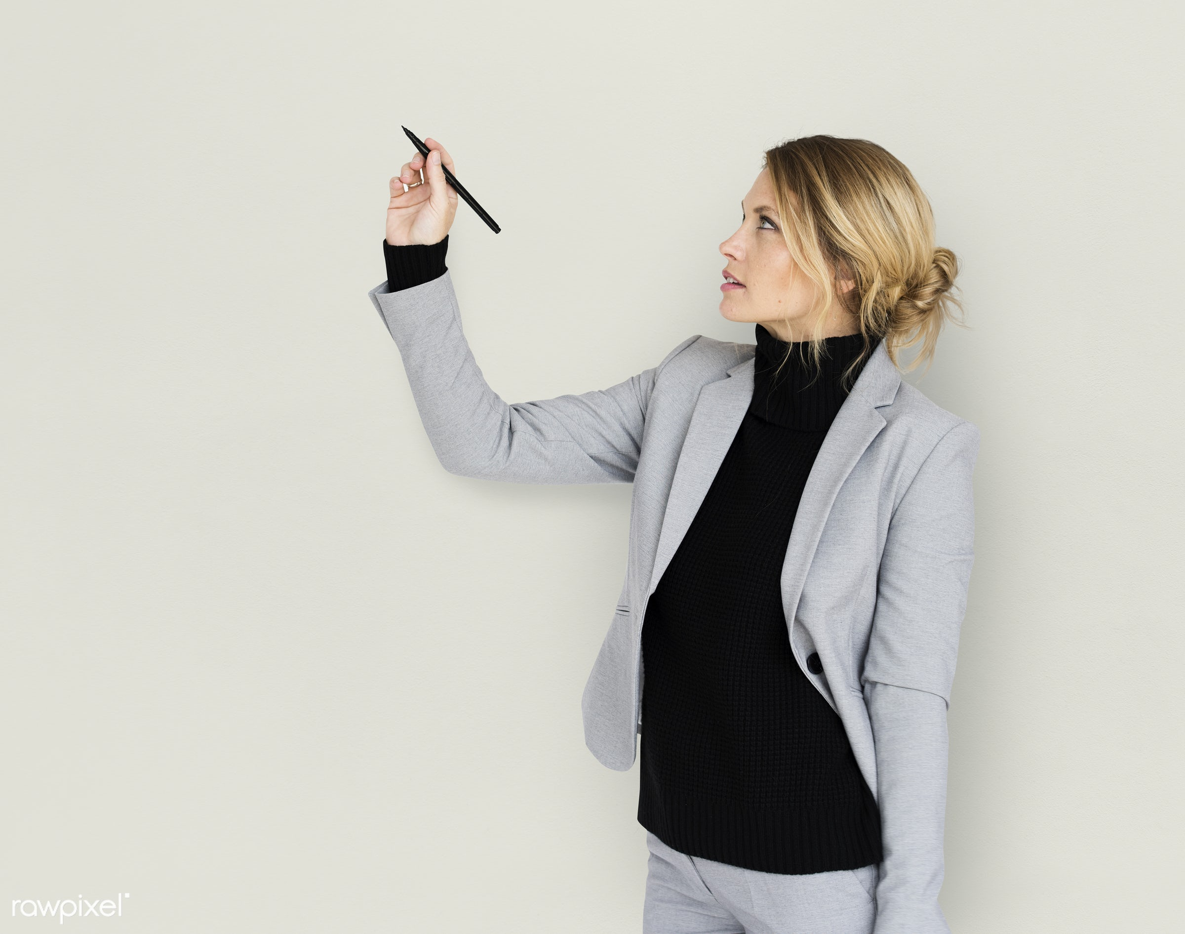 Businesswoman drawing with a pen - expression, studio, lecture, person, business wear, holding pen, writing, concentrating,...