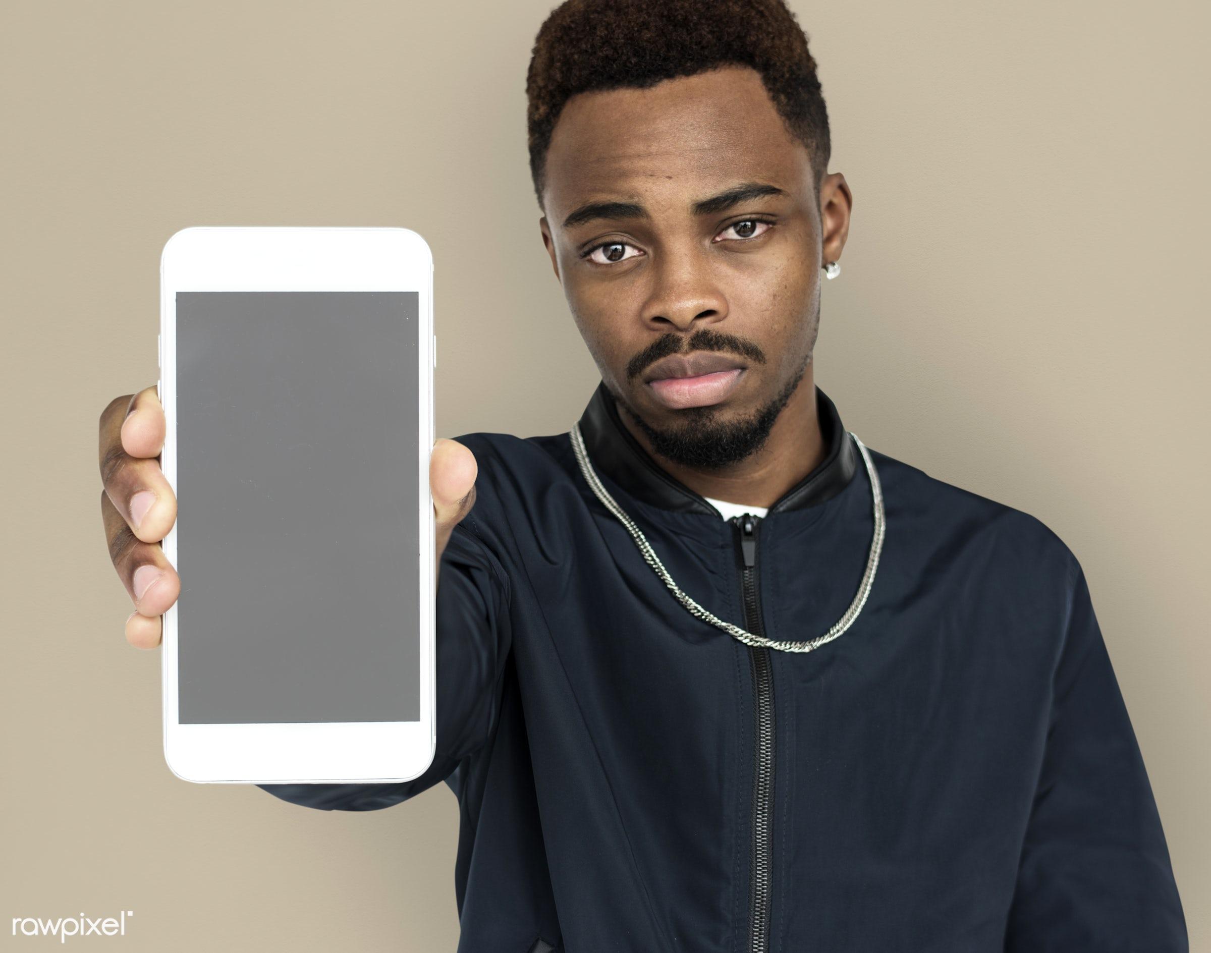 african descent, background, beard, black, brown, communication, device, emotion, expression, focused, holding, holding...