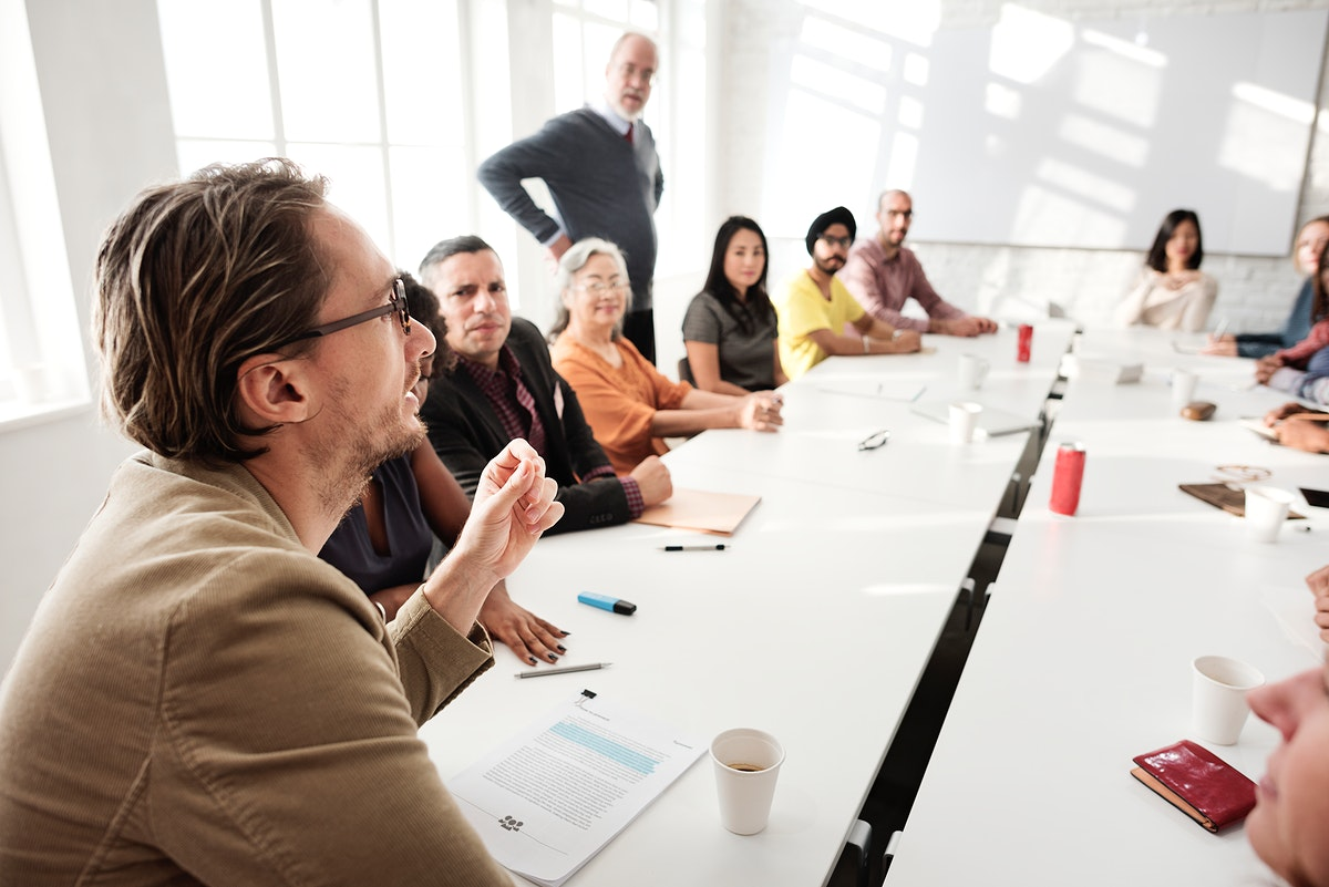 Guy leader talking to people at the meeting table