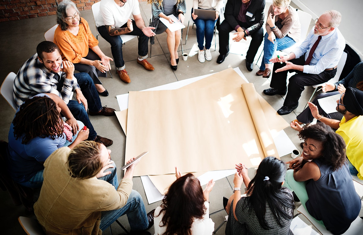 Seated people surrounding a sheet of paper on the floor
