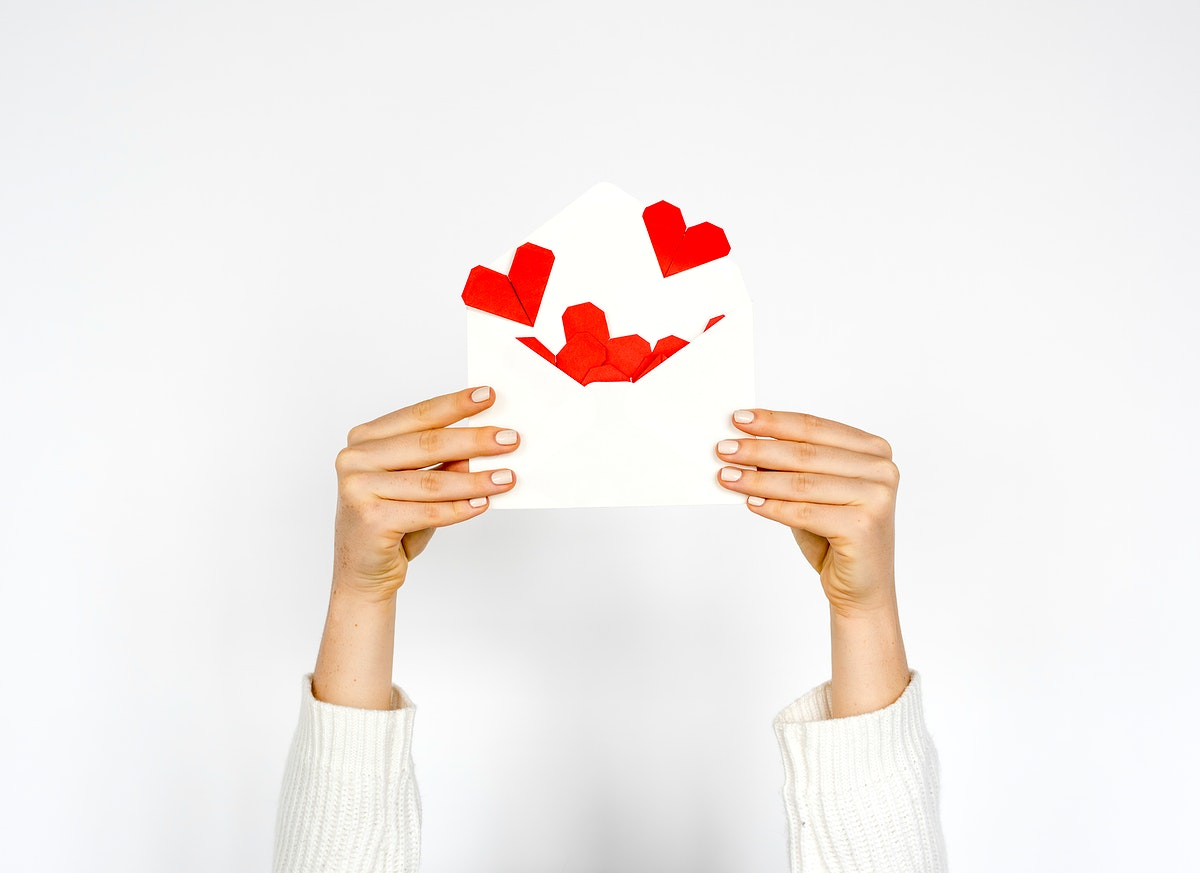Hands holding envelope with hearts inside on white background