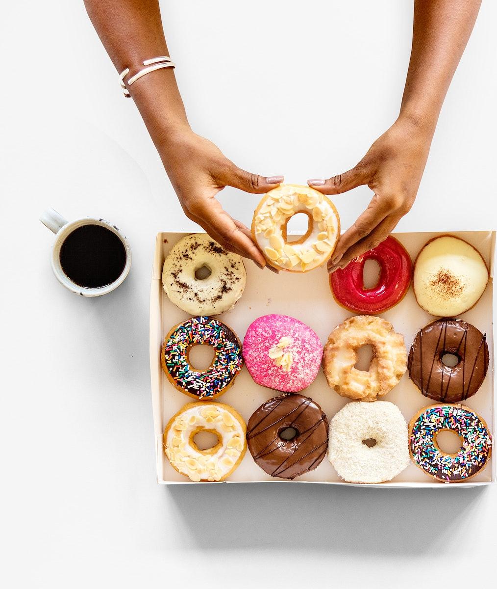 Hands holding sweeten donut dessert in aerial view