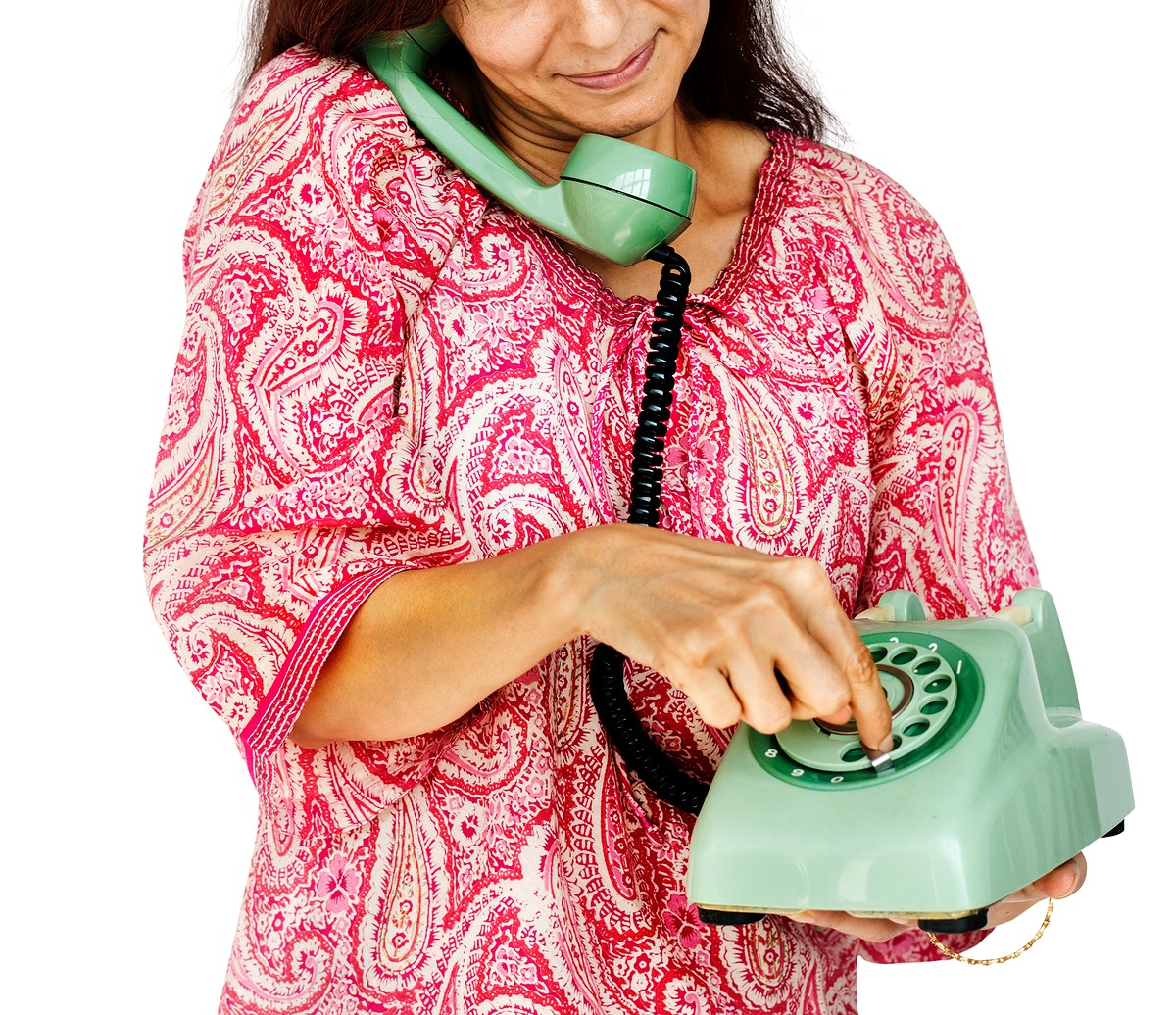 A woman is talking on a telephone