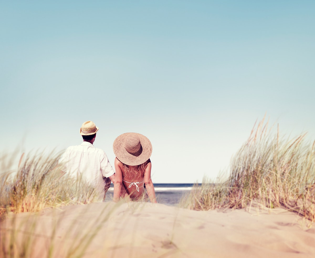 Rear view of couple sitting together at the beach