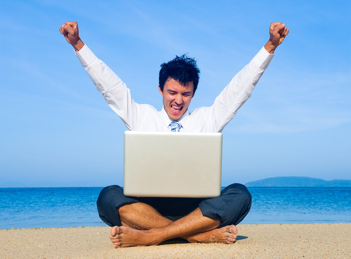 Business man on beach with laptop