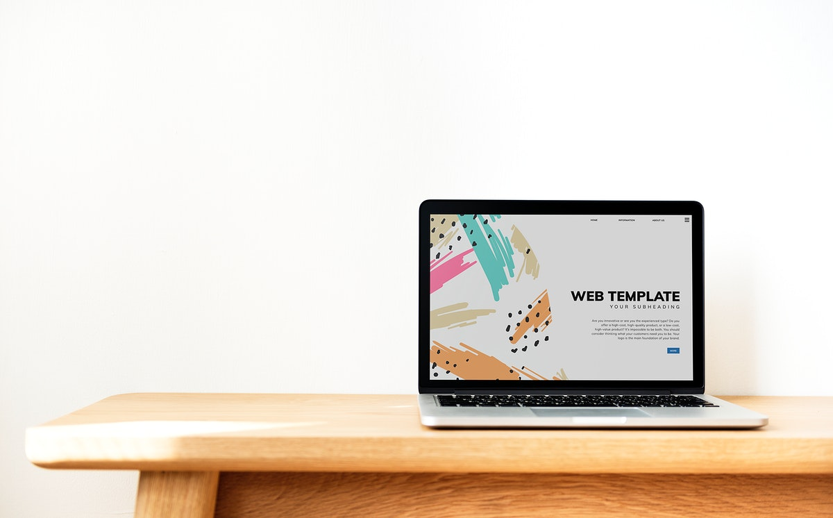 Laptop showing website template on a wooden table