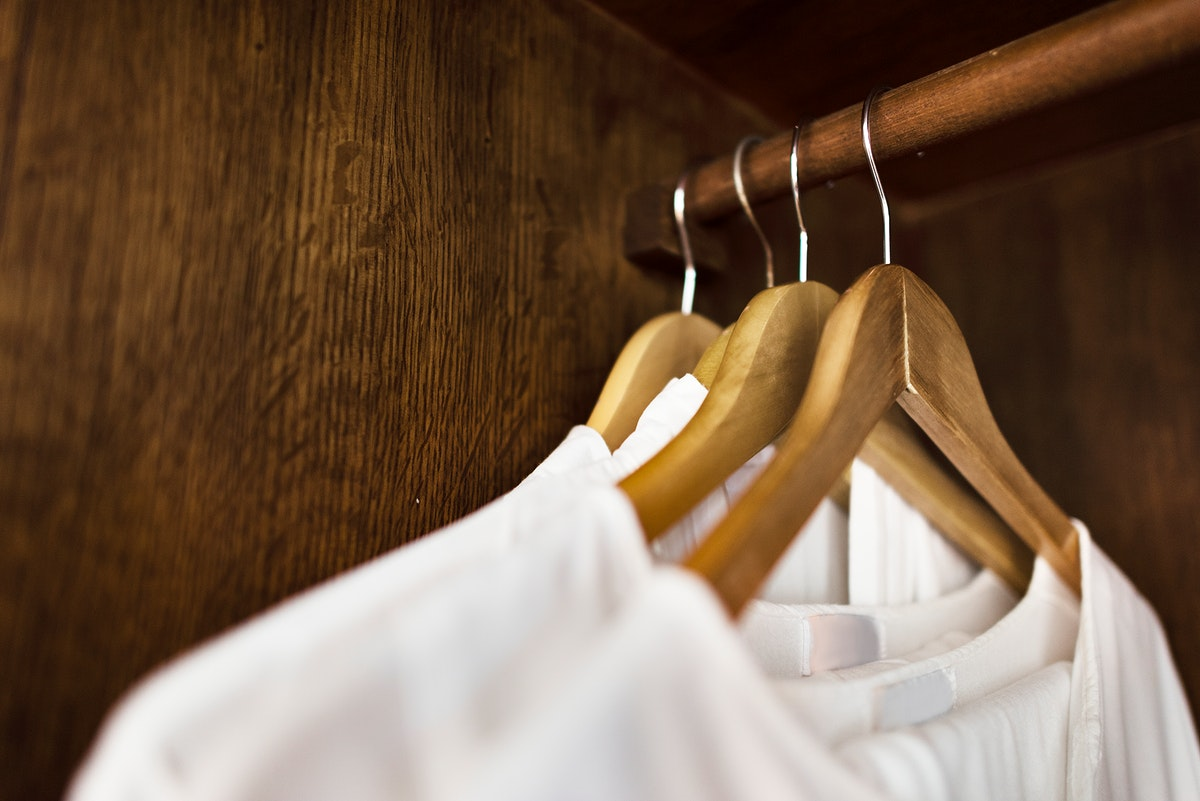 White clothes hanging in a wardrobe