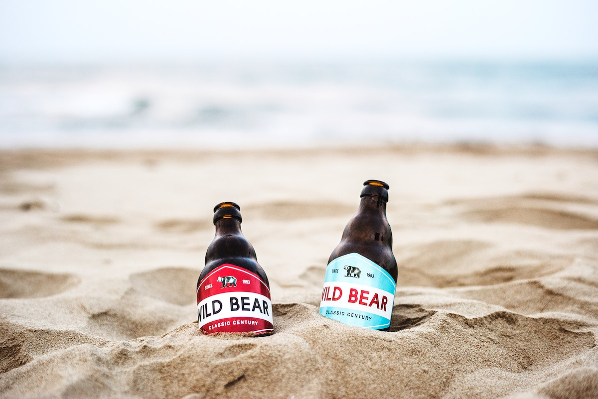 Two beer bottles buried in the sand