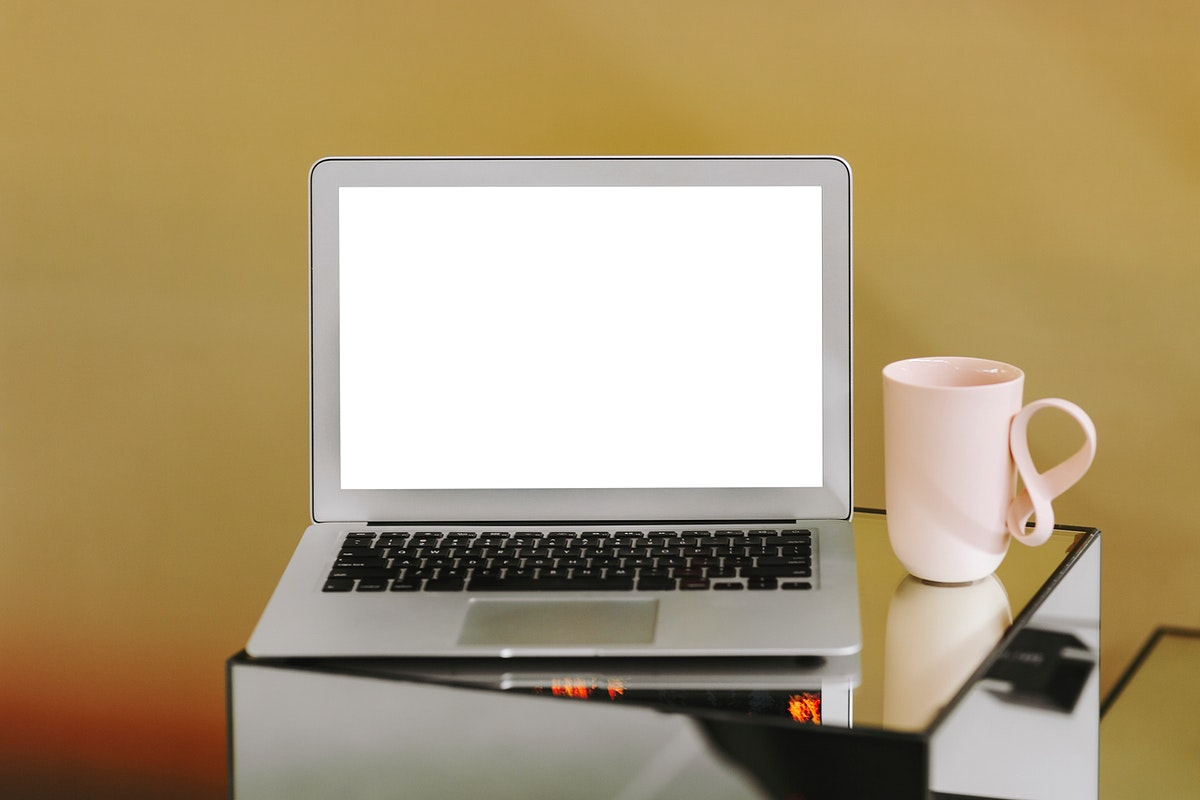 Blank laptop screen and a pink coffee cup