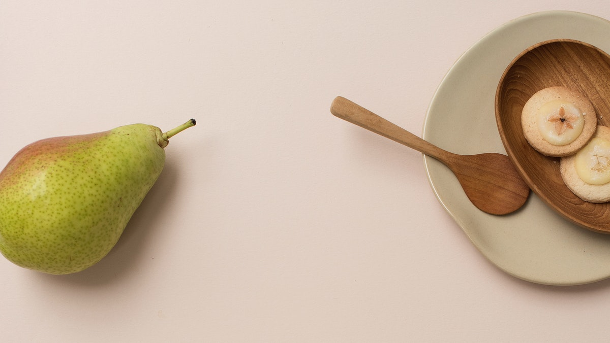 A pear and cookies on the table
