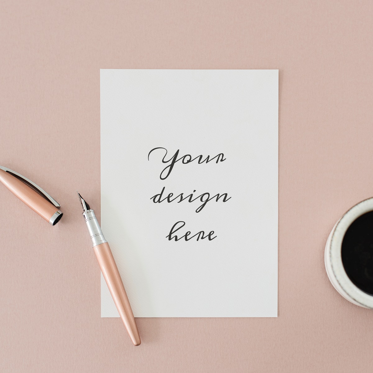 White paper mockup by a coffee cup on a pink table flatlay