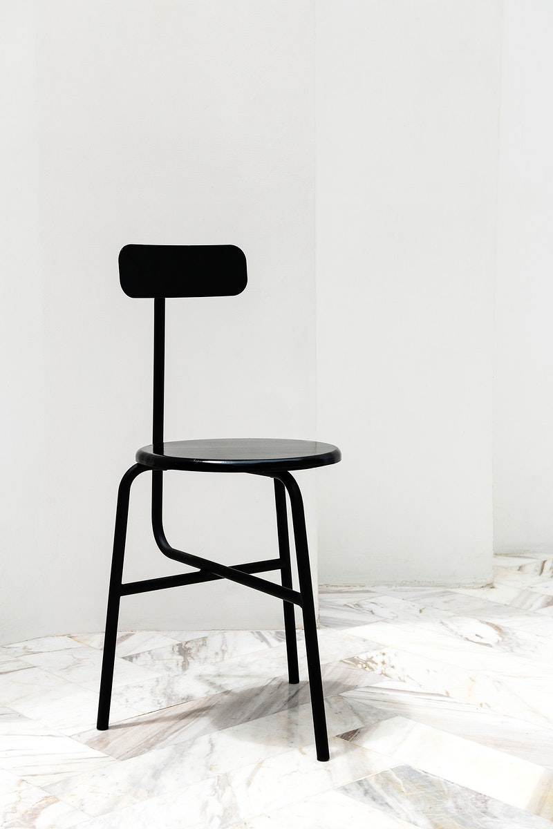 A black modern chair on a white marble floor