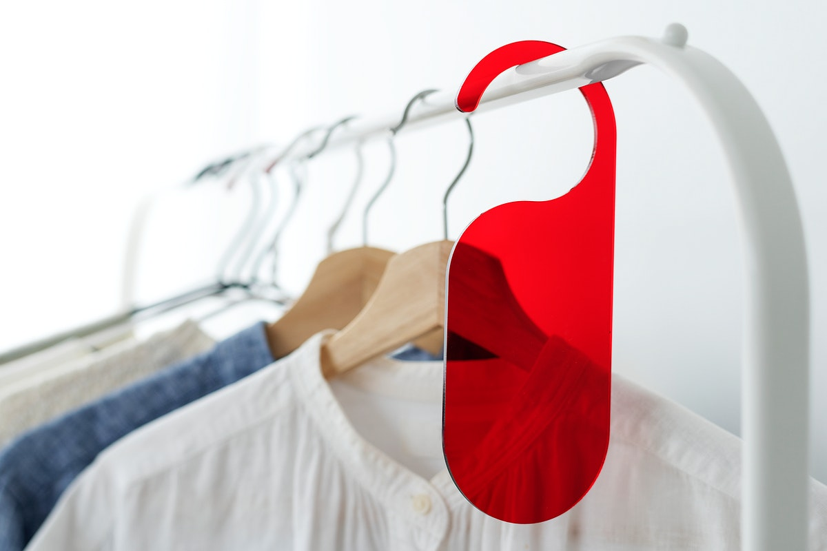 Shirt on a clothing rack with a red tag mockup in a studio