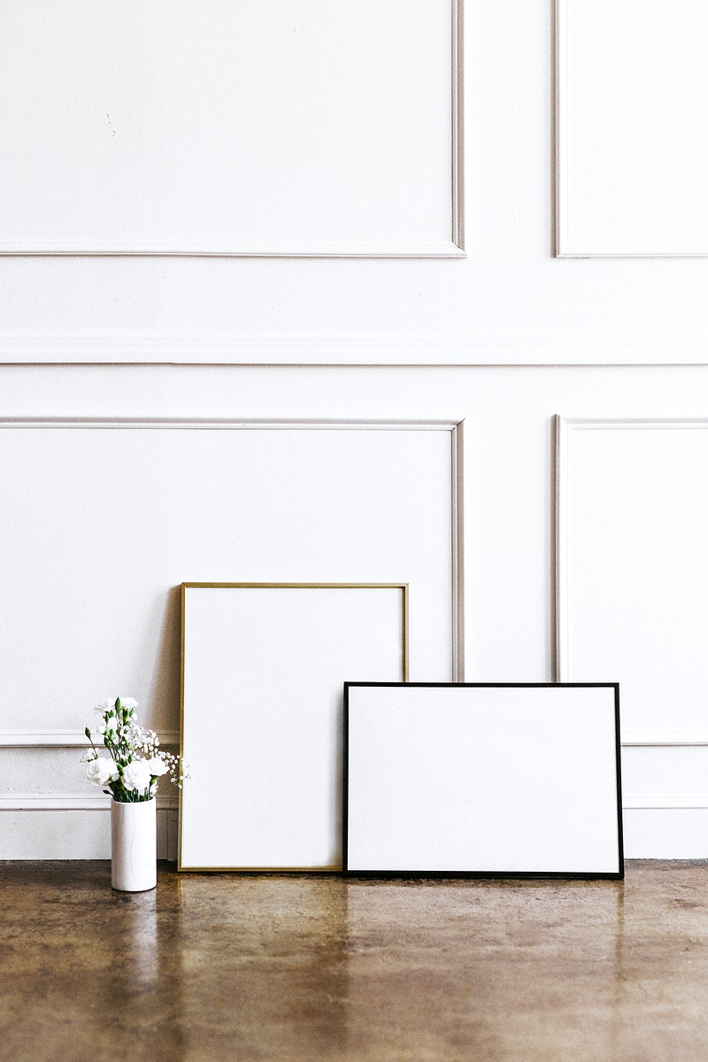 Frame against a white wall by a vase of flowers