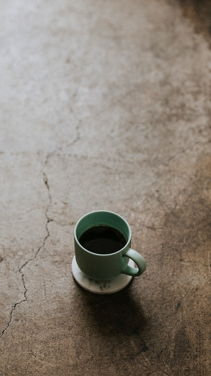 Hot cup of coffee on concrete floor mobile phone wallpaper