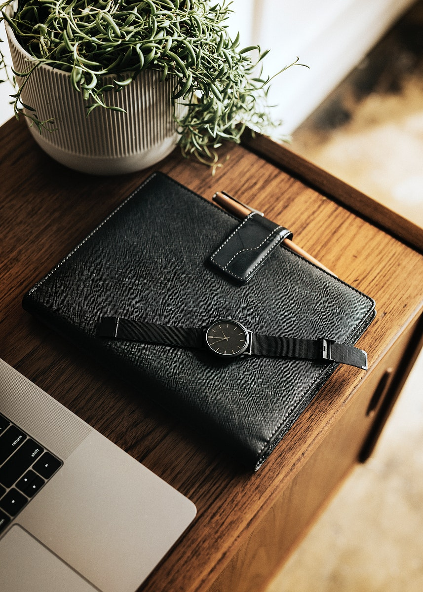 Black planner on a wooden desk by a laptop