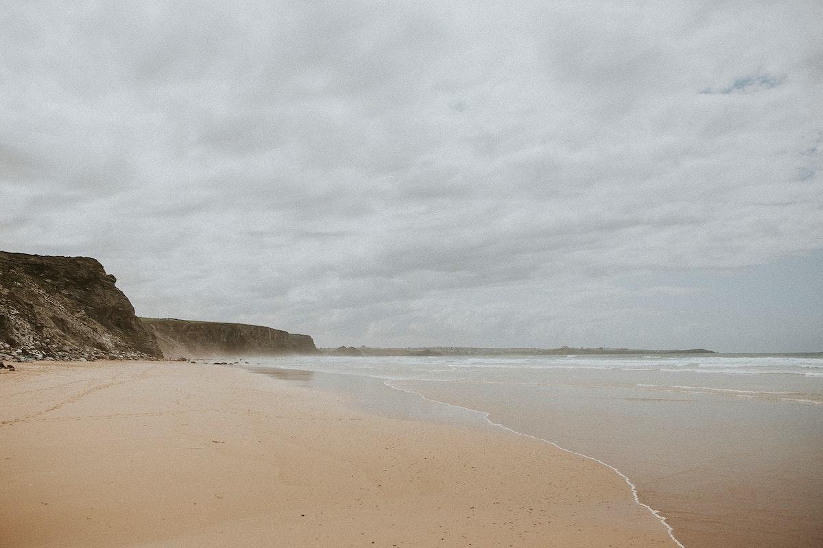 Hazy beach by a cliff
