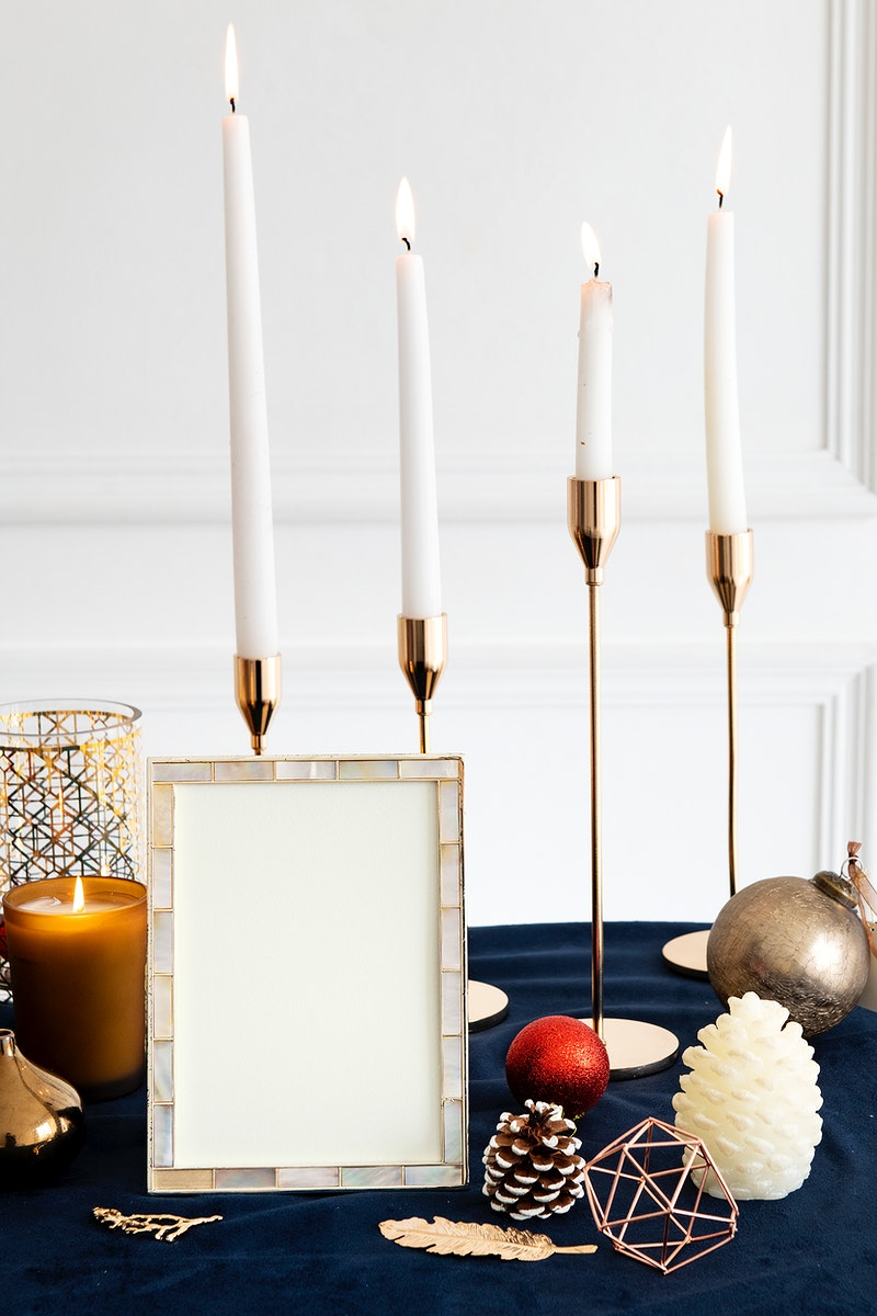 Christmas photo frame on a table with taper candles