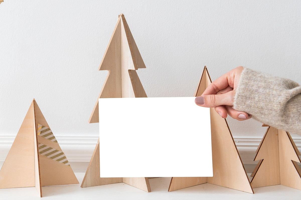 Greeting card in front of a paper Christmas tree mockup