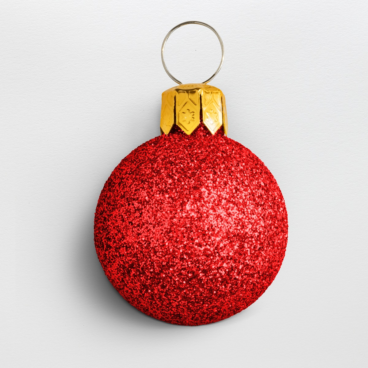 A glitter red ball Christmas ornament isolated on gray background