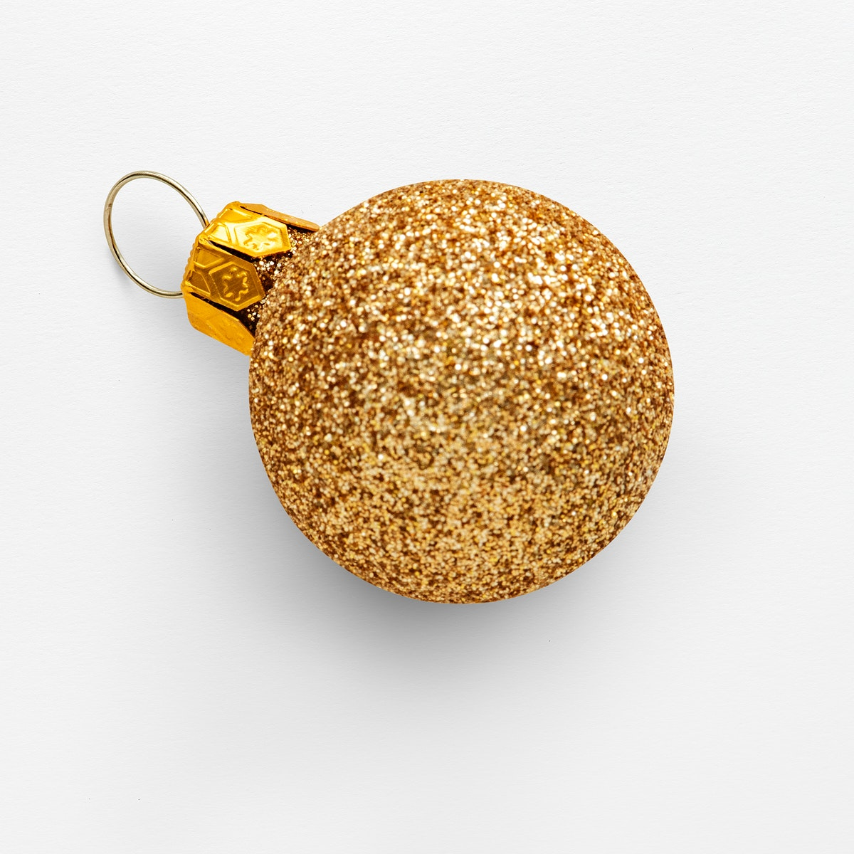 A glitter gold ball Christmas ornament isolated on gray background