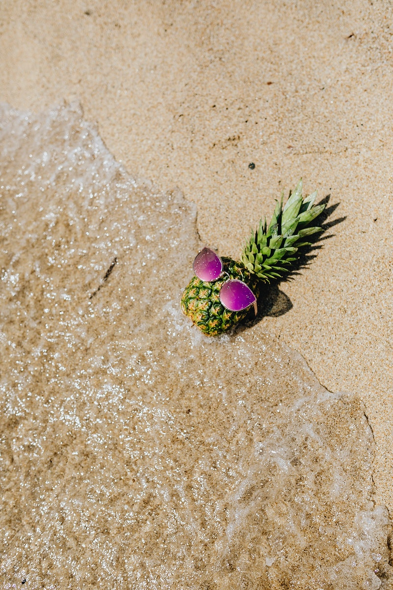 Fresh pineapple with a pink sunglasses lying at the beach