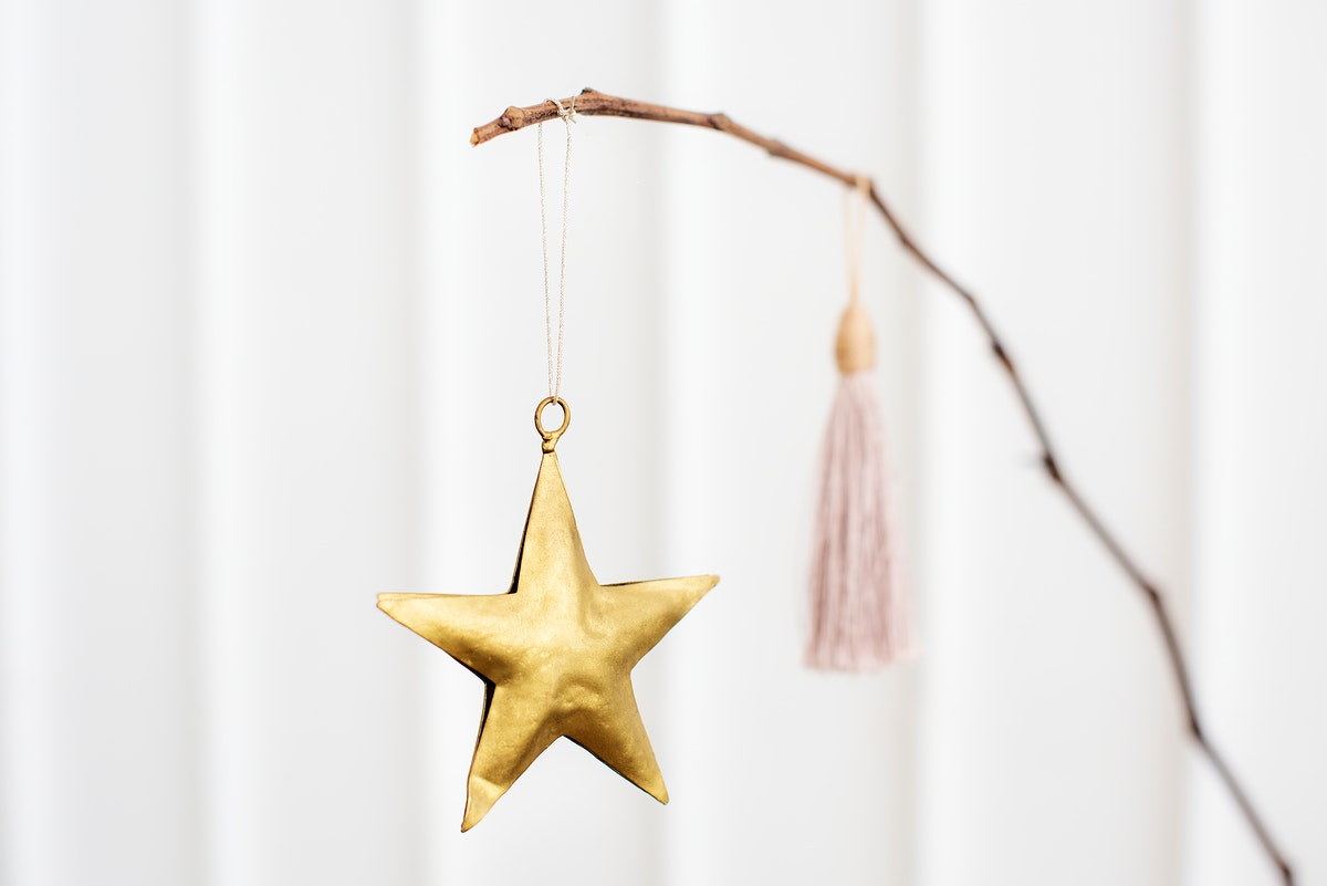 Golden festive star hanging on a branch