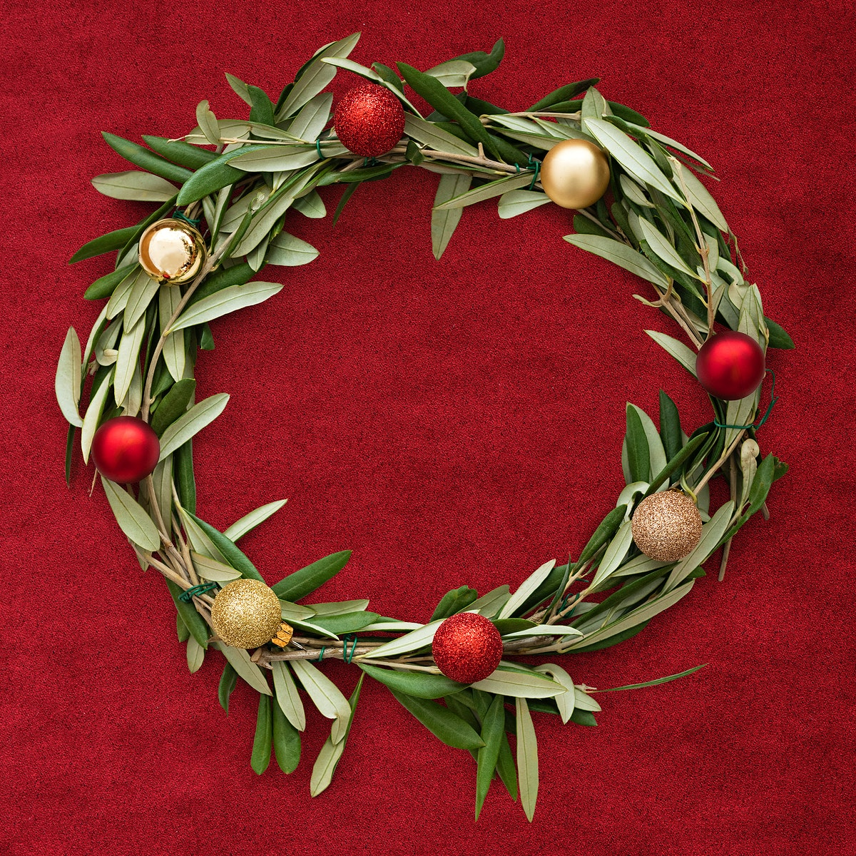 Handmade Christmas wreath decoration on a red fabric background