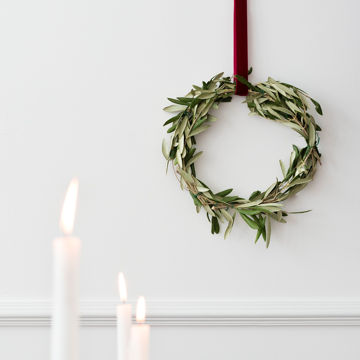 Christmas wreath on a white wall with lighted white pillar candles