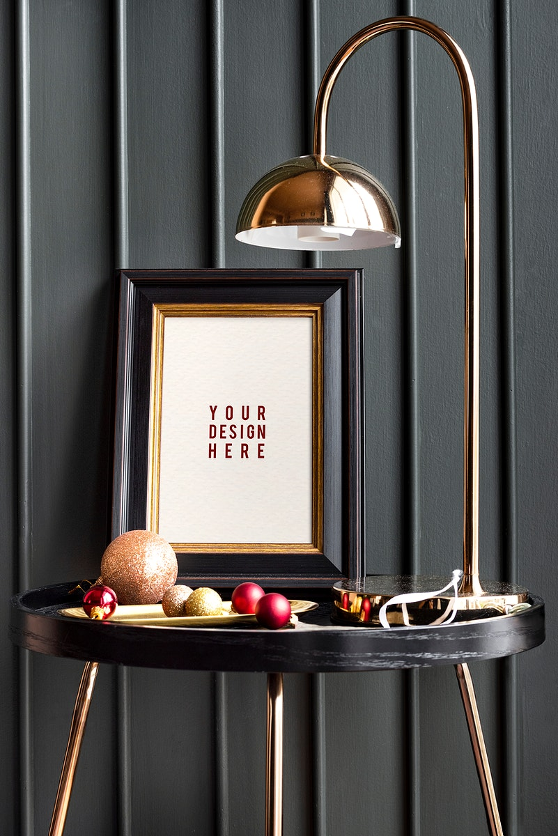 Black frame on a table with Christmas ornaments