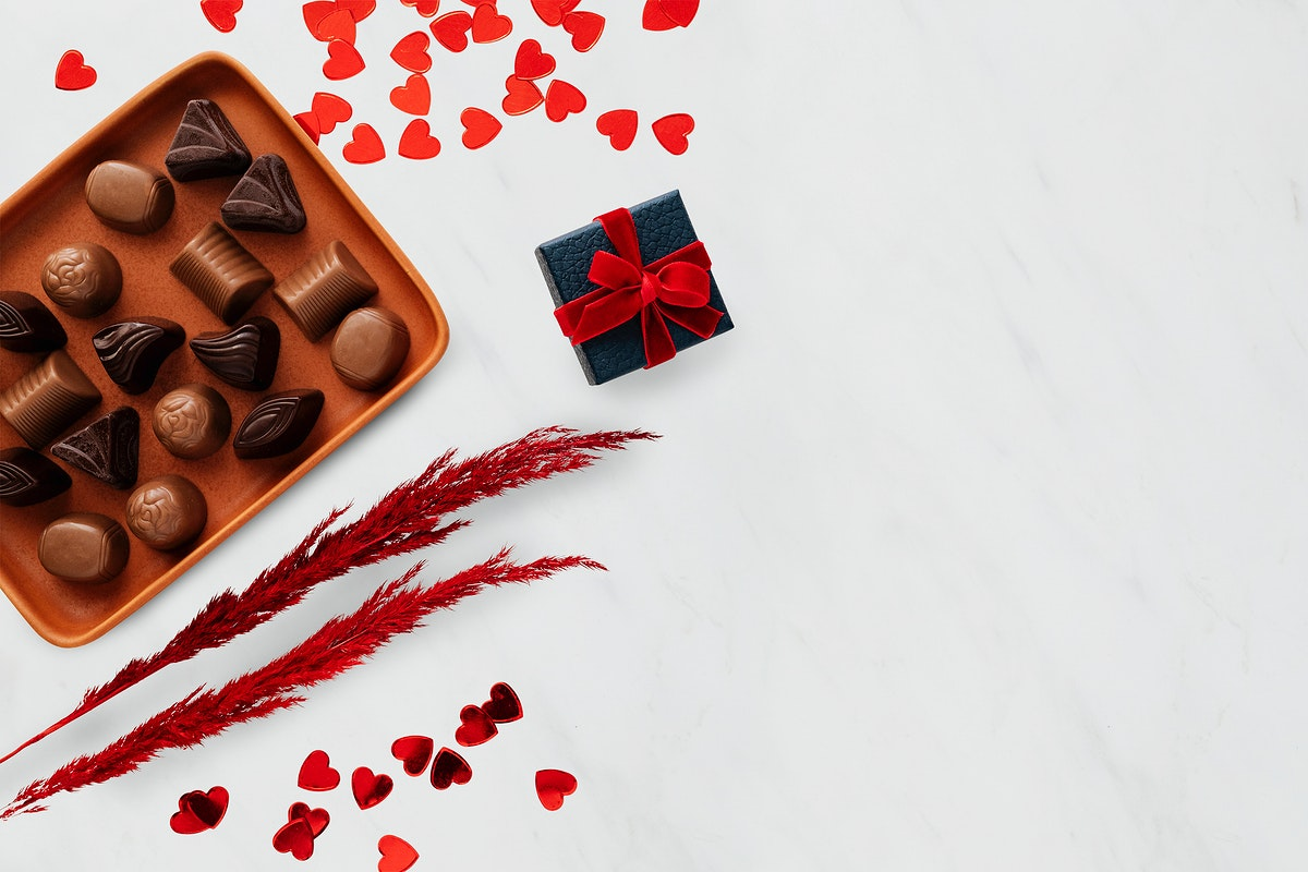 Chocolates on a tray by paper hearts