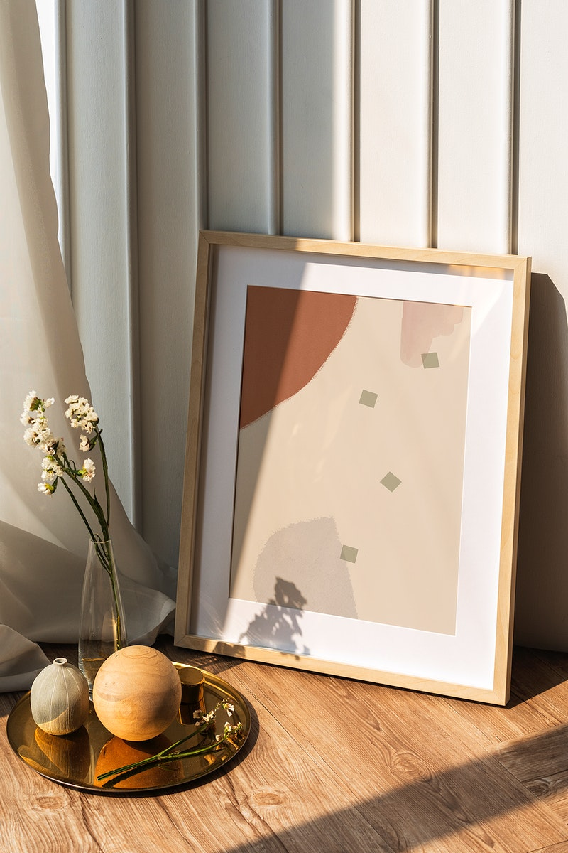 Picture frame mockup by a white wall on the wooden floor