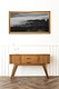 Picture frame mockup over a wooden sideboard table with taper candle holders