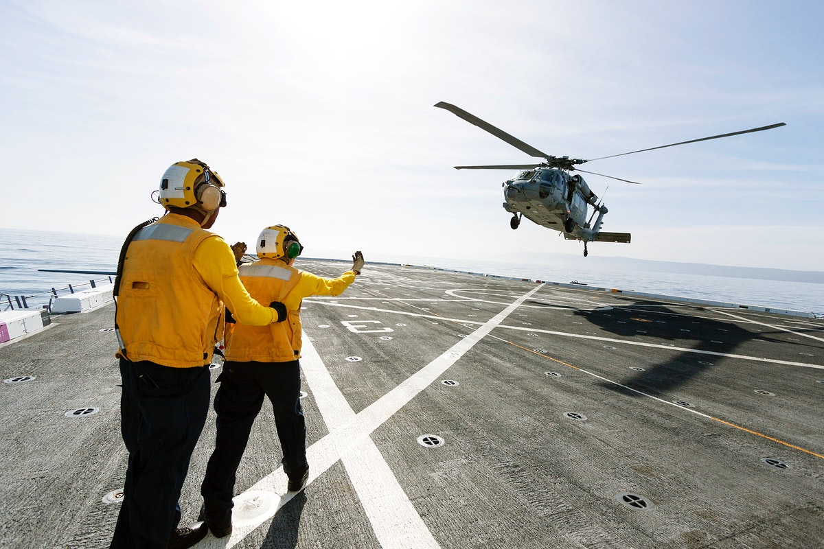 On the top deck of the USS San Diego, U.S. Navy personnel monitor a helicopter landing. Original from NASA. Digitally…