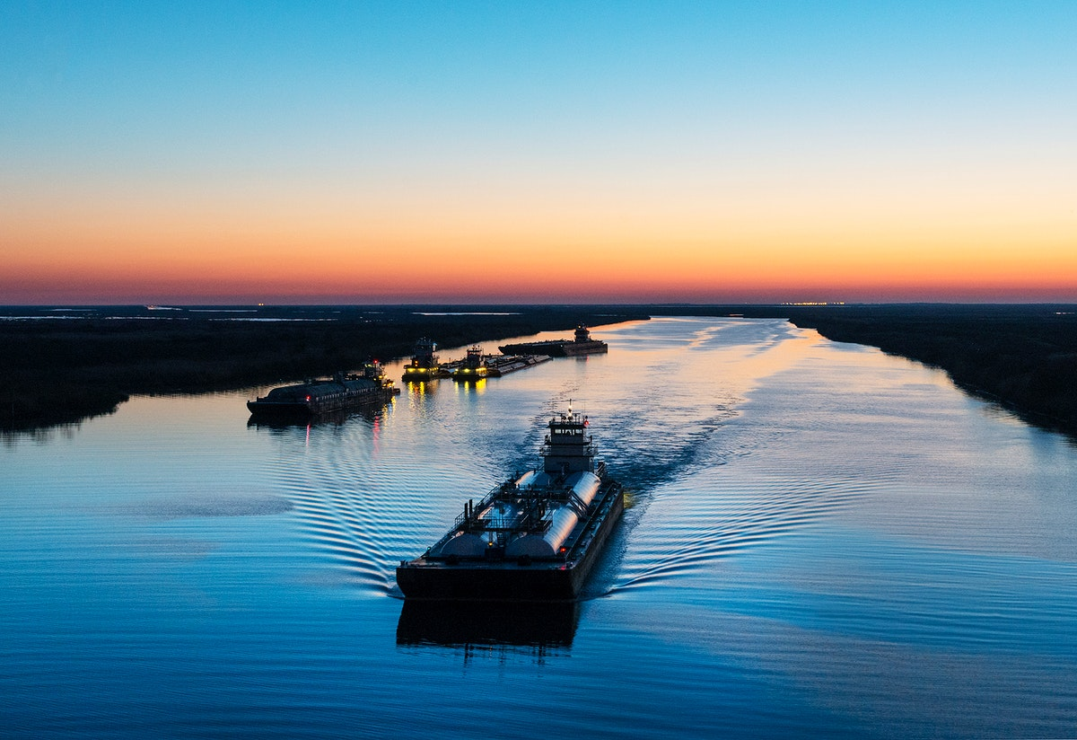 Dusk shot of barges traversing a short canal that connects the Sabine Pass waterway separating Texas from Louisians, and the…