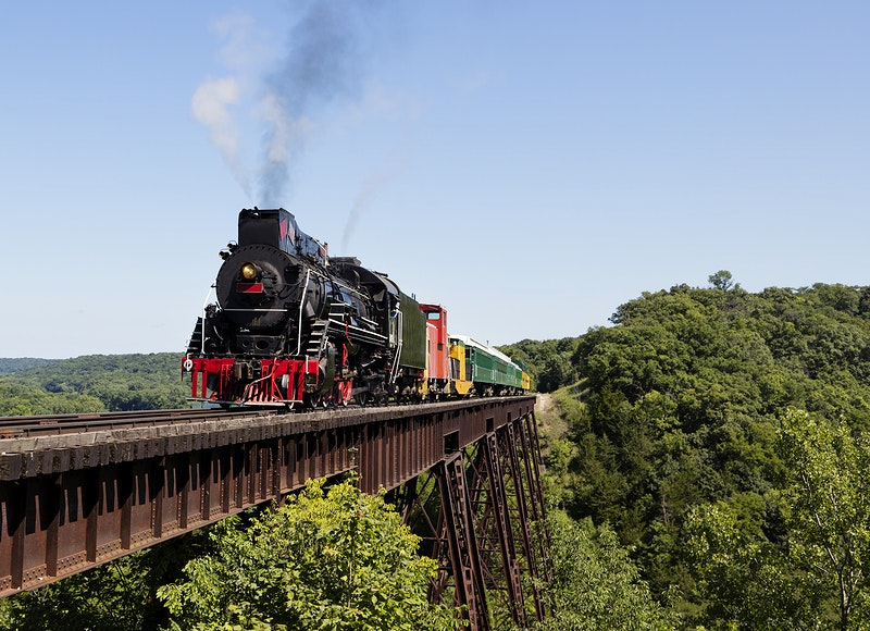 A steam train on a heritage railroad that operates excursions in Boone County, Iowa, crosses the 156-foot-tall Bass Point…