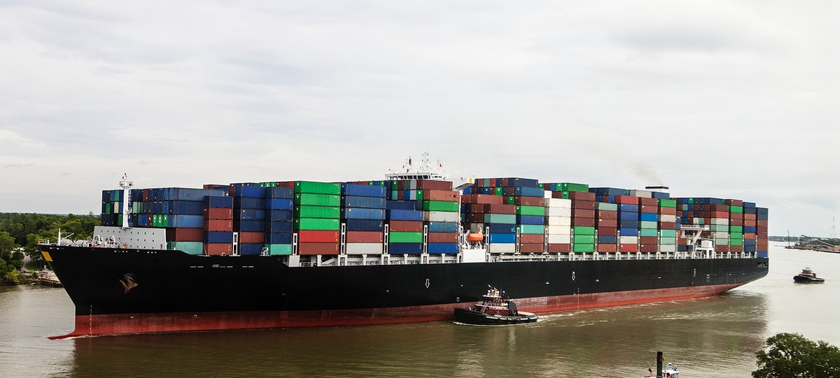 With a tugboat's help, an exceptionally heavy-laden oceangoing container ship plies the busy Savannah River in Savannah…