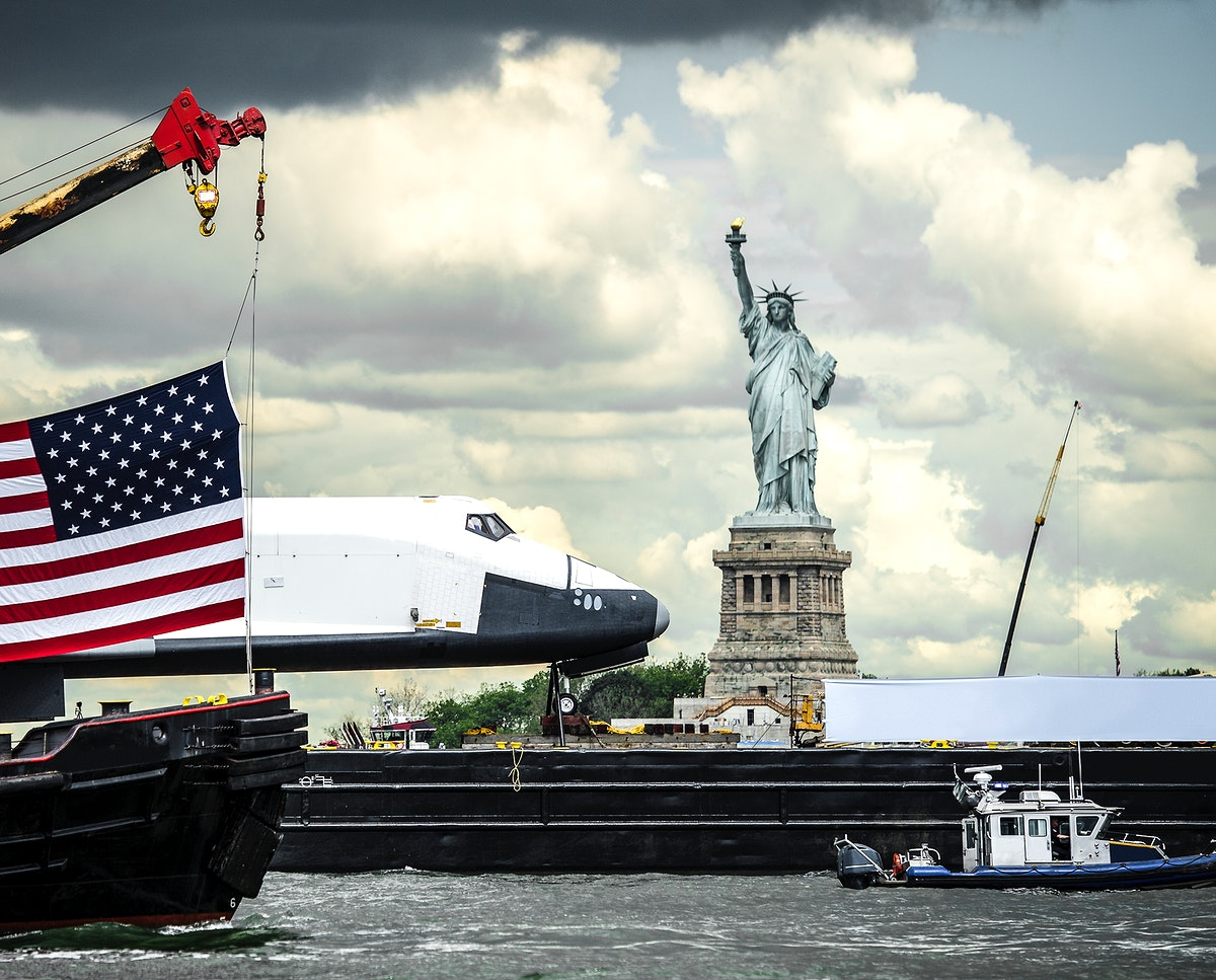 The space shuttle Enterprise, atop a barge, passes the Statue of Liberty in New York. Original from NASA . Digitally enhanced…