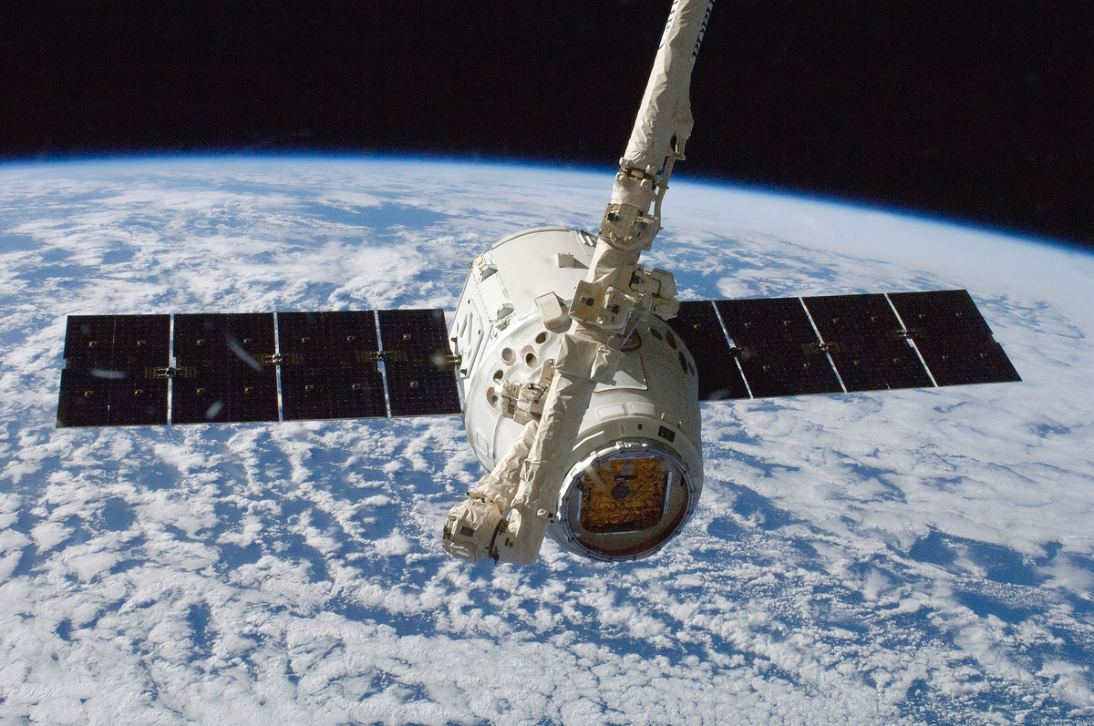 The SpaceX Dragon commercial cargo craft is grappled by the International Space Station's Canadarm2 robotic arm. Oct…