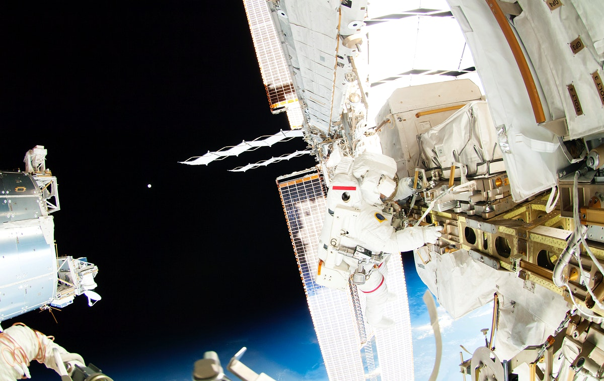 Astronauts working outside the space station's Quest airlock in Oct 7, 2014. Original from NASA . Digitally enhanced by…