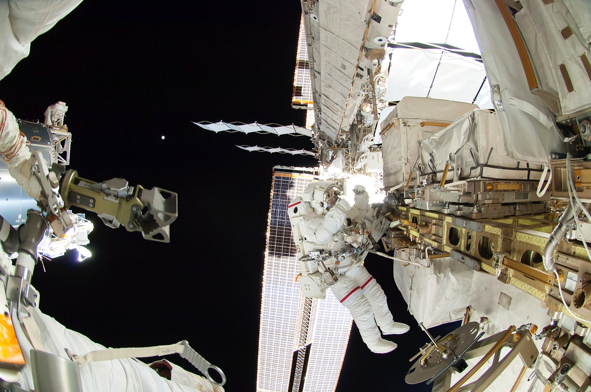Astronauts working outside the space station's Quest airlock in Oct 7, 2014. Original from NASA. Digitally enhanced by…