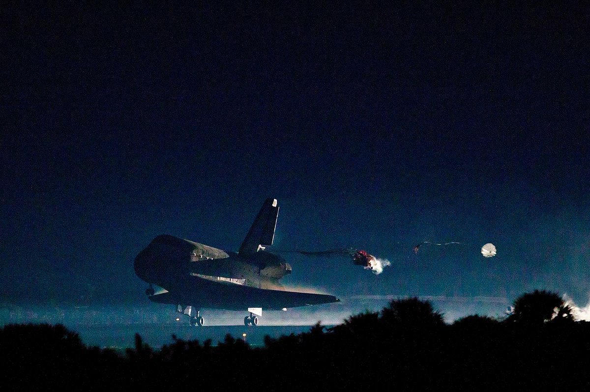 The drag chute is deployed as the space shuttle Atlantis lands on July 21, 2011 at the Kennedy Space Center in Florida.…