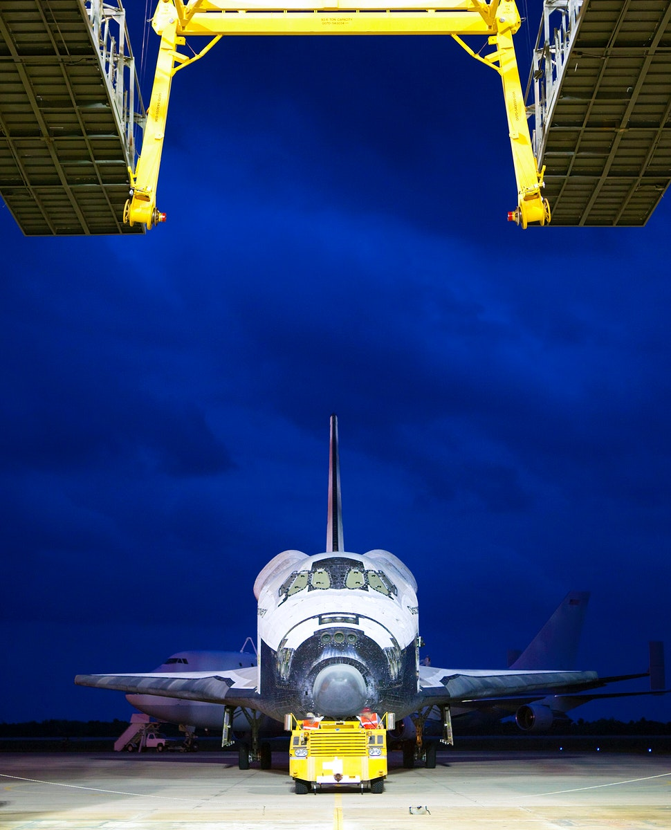 Space shuttle Discovery is towed into position at the mate-demate device, at the Shuttle Landing Facility, at NASA's…