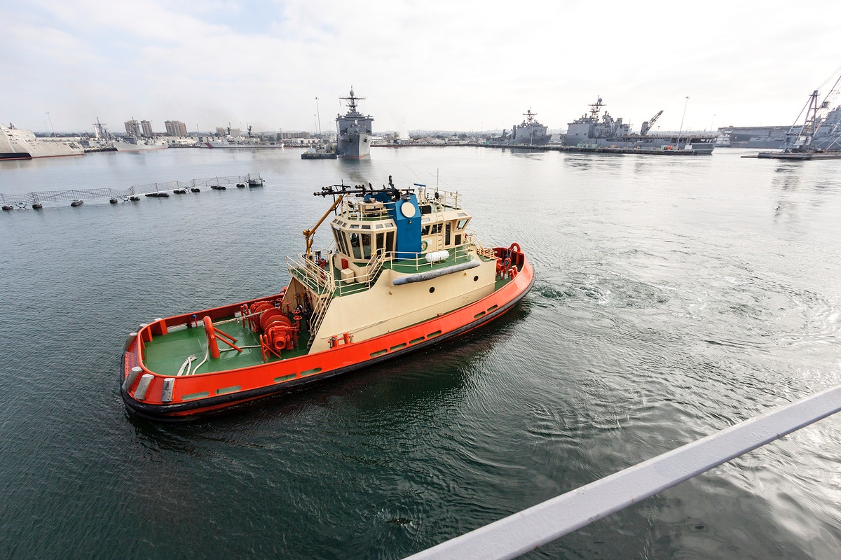 At the U.S. Naval Base San Diego in California, a tug boat accompanies the USS San Diego as it departs for open seas in the…