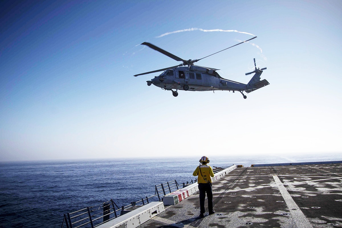 An H60-S helicopter takes off from the deck of the USS Anchorage during the first day of Orion Underway Recovery Test 3…