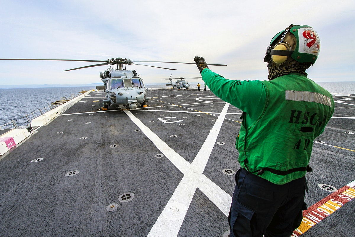 SAN DIEGO, Calif. – A member of the Helicopter Sea Combat Squadron 8 signals to the pilot in an H60-S Seahawk…
