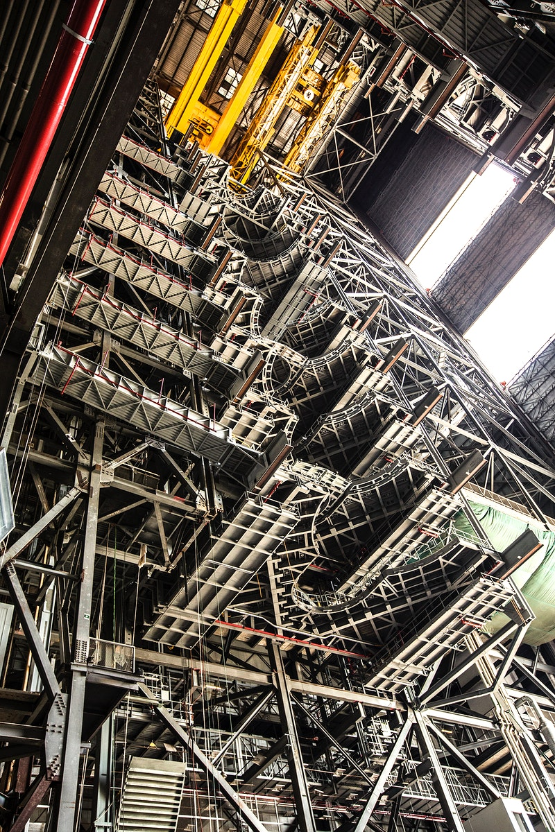 High up in the Vehicle Assembly Building (VAB) at NASA's Kennedy Space Center in Florida, a crane lowers the second half of…