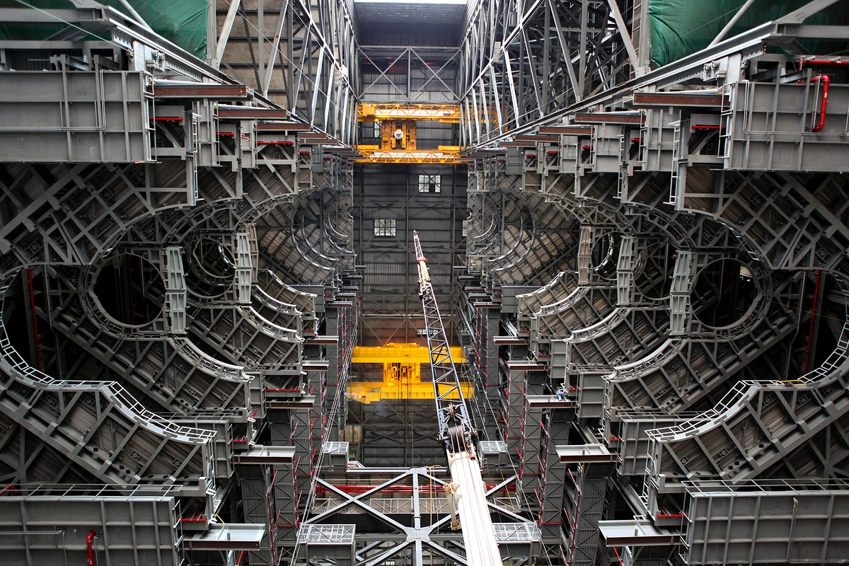 High up in the Vehicle Assembly Building (VAB) at NASA's Kennedy Space Center in Florida, an overhead crane has lowered the…