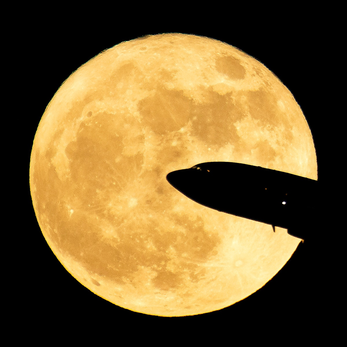 Aircraft taking off from Ronald Reagan National Airport is seen passing in front of the Moon as it rises in Washington…